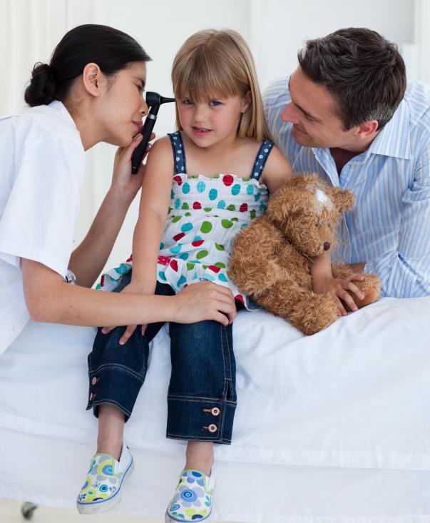 Помощник педиатра лечит маленьких пациентов под наблюдением педиатра.