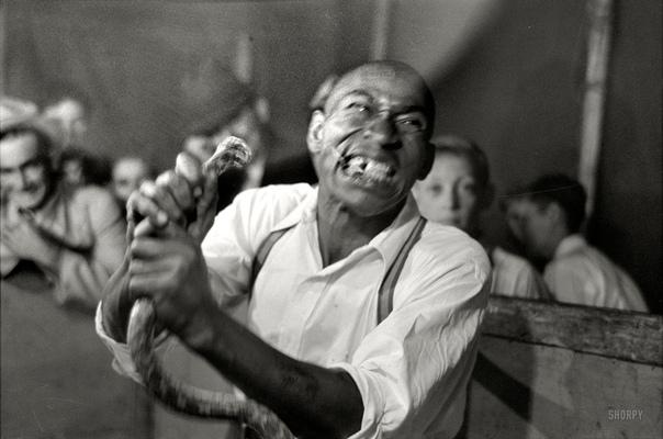 Ноябрь 1938 года Человек, откусивший голову змеи, развлекает посетителей ярмарки в Дональдсонвилле, штат Луизиана. фотограф Рассел