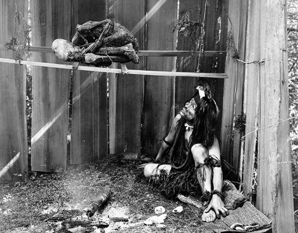 На этом фото образца 1910 года запечатлено, как индеец из племени Квакиутл сушит мумию родственника, которую затем планирует использовать в ритуальных целях